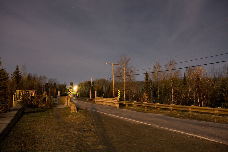 Charlton, Ontario, under a full moon. Highway 574 heading west across a single lane bridge over the Englehart River. This shot has some illumination from a street light which provides a shadow of the photographer.