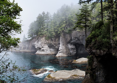 Sea caves, looking back from the tip of Cape Flattery. The sea caves represent the early stages of the formation of sea stacks. A point of land is eroded and undercut, forming caves, then arches. When the arches collapse, they leave sea stacks.