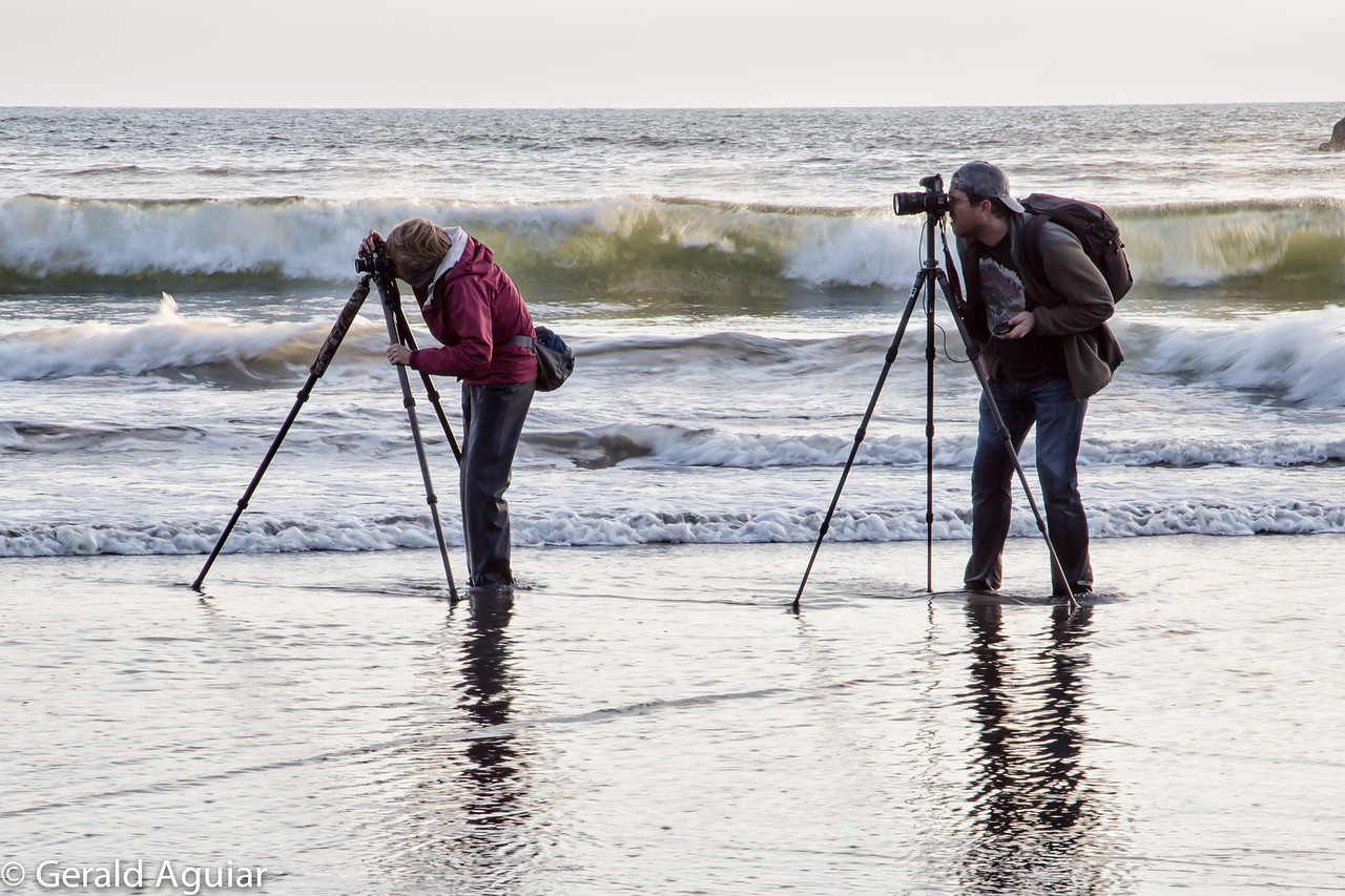 """Instructor Tim Grey and a student wading into the surf getting the """"shot""""."""
