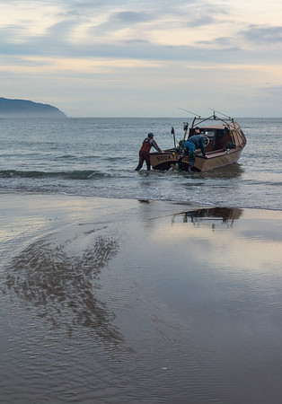 They back the boat on its trailer into the ocean, then quickly stop and drive away, causing the boat to slide into the water. One or two men turn it around, push it a little deeper, then climb on.