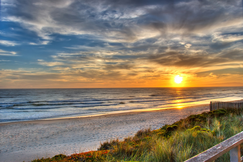"""Pajaro Sunset"" Pajaro Dunes, California Sunset and Ocean during summer.  This is one of those images I captured while on vacation with our family.  We were staying with friends at this nice house right on the beach (the kind of setting you don't want to ever leave!)   The sun was low in the sky with nice clouds and color.  I could hear the waves crashing on the beach below.  I shot this off of the deck of our house including the tall grasses, fence and red wildflowers that really completed this shot.  This is one of those places that I want to be on a Friday afternoon."