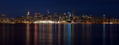 Vancouver Skyline / Vancouver B.C. / Canada  The skyline from outside the Lonsdale Quay public market in North Vancouver. Was searching for a place to shot the downtown with some reflection in the water. Shot one from Stanley park, but I like this better because of the different colors getting reflected in the water. This is a panorama stitched by combining multiple images using Microsoft ICE. It is a 41 megapixel image - a compressed version is displayed above.  For Deep Zoom (to get more details in the photo) check out this link: http://zoom.it/Im76#full
