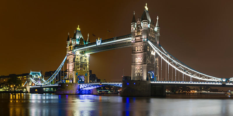 """""""Tower Bridge at Night""""  London, England, United Kingdom. This summer I had a business trip to London and we stayed just down the way from the Tower Bridge. I headed out to capture some shots at night as the bridge is nicely lit at night and the reflections on the River Thames looked fantastic! Another one of those fantastic places to visit!  <br /> <br /> I created this image with 6 Nikon D800 images and the Nikon 24-70 f/2.8 lens, f/16, 30 second exposures, ISO 100.  Processed in Lightroom 4 and exported as 16 bit TIFFs.  The Panorama was stitched in Autopano Giga 3.0 from and cropped to a 1:2 panorama.  Nothing better than lots of pixels to make ginormous panoramas!!  Can't wait to print this one.   Night photography in London is fun and can't wait to go back!   One note- don't wait too late as they turn off the lights at the Tower of London, Majesty's Royal Palace and Fortress, around 11pm!  I was hoping to include that lit up but missed it!"""