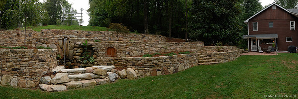"""This stone wall was constructed over a period two or three years at a private residence near Durham, NC.  The craftsman who designed and built the wall collected stones from chimneys of 17 abandoned homes within a 30 mile radius of this site as well as stones from the edges of farm fields in Person County, NC.  The wall serves as a retaining wall in this landscape at the end of a road and along the residence's drive.  The scale of the work created the first and strongest impression to me.  Once over the initial impression, I was able to take in and appreciate some of the complexity of the overall plan as well as the intricacy of the assembly and variety of incorporated ornamentation.  This panorama shows about 80% of the wall.  Details from the wall, including the water fall and steps may be seen in <a href=""""http://www.alechimwich.com/Architecture/Interior-and-Exterior-Home"""">Interior and Exterior Home Embellishments</a>."""