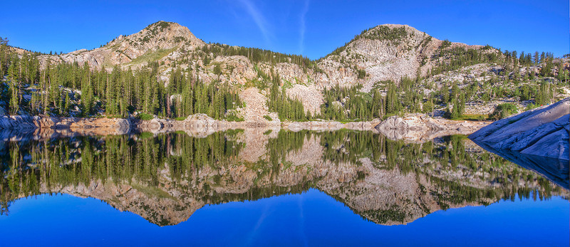 The rocky slopes of Mount Tuscarora (left) and Mount Millicent (right) reflect in the still waters of Lake Mary, Big Cottonwood Canyon, Wasatch Mountains on an early summer morning.