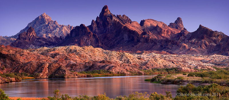 The Colorado River runs through the Mojave Desert's Topock Gorge at dusk on the California Arizona border.
