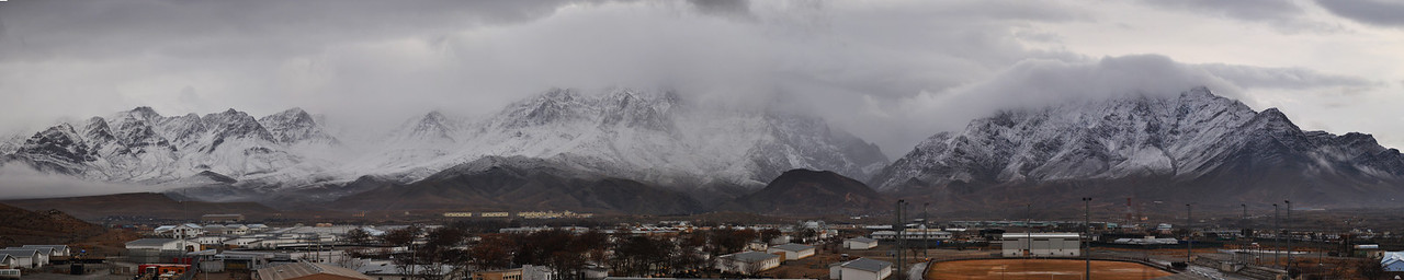 Clouds bathe the mountains surrounding Pol-e-Charki, Afghanistan in mist and snow - because of the extreme panormic size of this image, please contact me for orders.