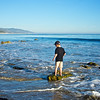 Boy stands on a rock in the waves and ripples of the Pacific Ocean.