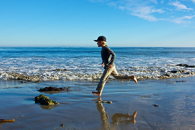 A boy runs along the edge of the waves on the California shore of the Pacific Ocean.