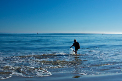 A boy kicks and splashes for fun in the warm Pacific Ocean of Malibu, California.