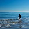 A boy kicks and splashes for fun in the warm Pacific Ocean of Malibu, California.
