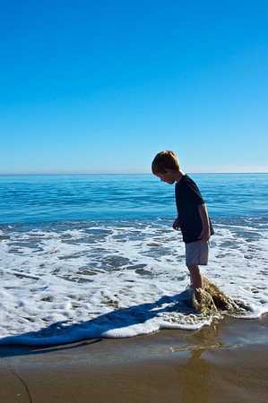 A boy sinks his toes into the refereshing cool water of the Pacific Ocean in Malibu, California.