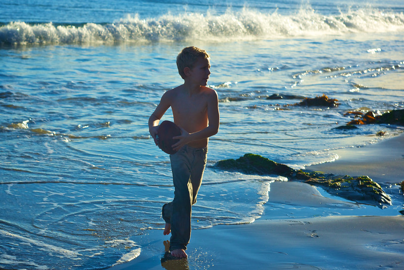 Playing throw and catch with a football in the Pacific Ocean.