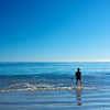 A young boy stands staring in the rippling waves of the Pacific Ocean in Malibu, California