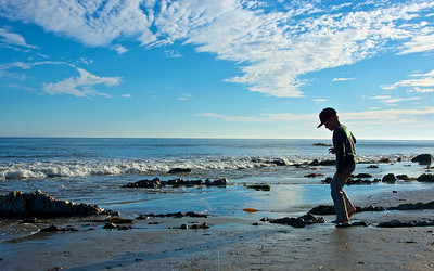 A young boy walks along the rocky shore of Malibu's Pacific Coast.