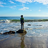 A boy stands alone on a stone above the small waves of the Pacific Ocean.