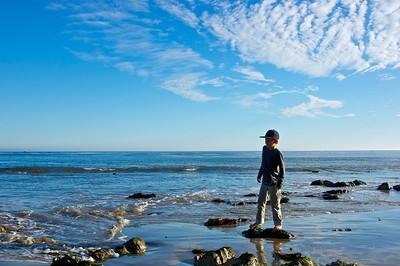 Boy keeps his feet out of the water by standing on a stone on the shore of the Pacific Ocean.