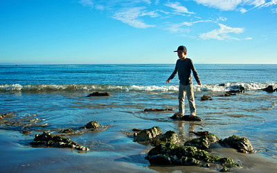 A young boy stands on the dry top of a rock along the Pacific Coast.