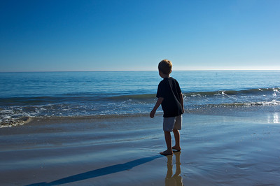 A young boy stares out across the calm blue waters of the Pacific Ocean in Malibu, California