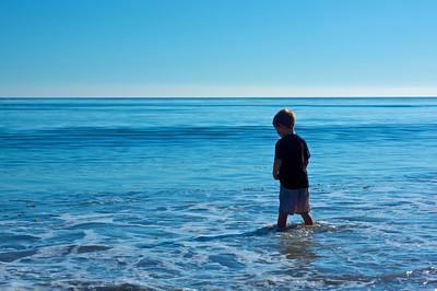 Boy stands knee-deep in the calm coastal waters of the Pacific Ocean near Malibu, California.