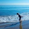 A boy runs along the Pacific Ocean's water in Malibu, California.