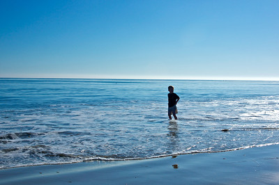 A young boy looks back toward land while standing in the shallows of the Pacific Ocean near Malibu, California.