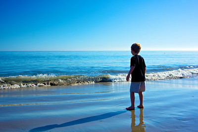 Young boy stands in the cool, watered sand of the Pacific Ocean in Malibu, California.