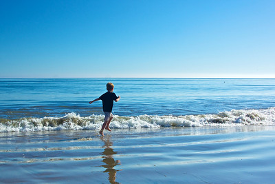 A boy runs through the surf, cool water of the Pacific Ocean in Malibu, California.