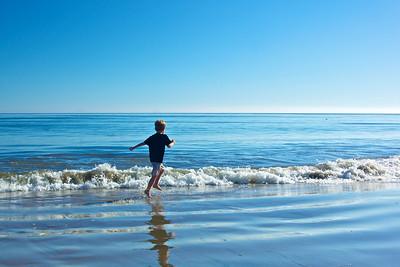 A boy runs through the surf, cool water of the Pacific Ocean in Malibu, California.