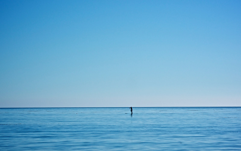 A man slowly paddleboards across the placid waters of the Pacific Ocean.