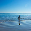 A young boy stands in the shallow rippling waves of the Pacific Ocean in Malibu, California