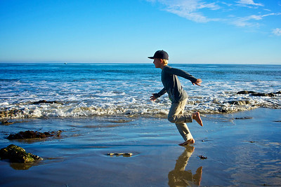 A adolescent boy runs along the oceanside of the Pacific in Malibu, California.