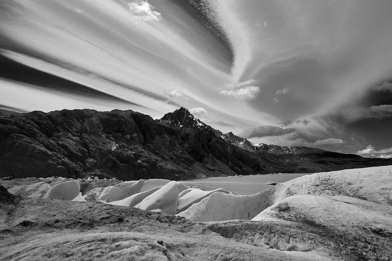 A windswept B&W shot of a very cold glacier and surrounding mountains.