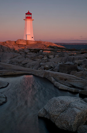 Dawn at Peggy's Cove lighthouse. Note the wind rippling the surface of the water in the foreground.