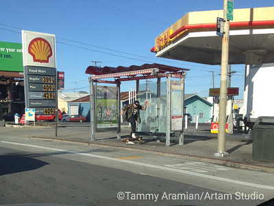 San Francisco in a nutshell #2: Middle-aged white man doing skateboard tricks at a bus stop with a bicycle usage ad in front of a gas station with a taxi behind it, July 2015.