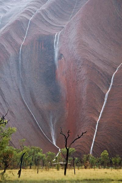 Rainstorm cascades down Uluru: Ayer's Rock, Australia