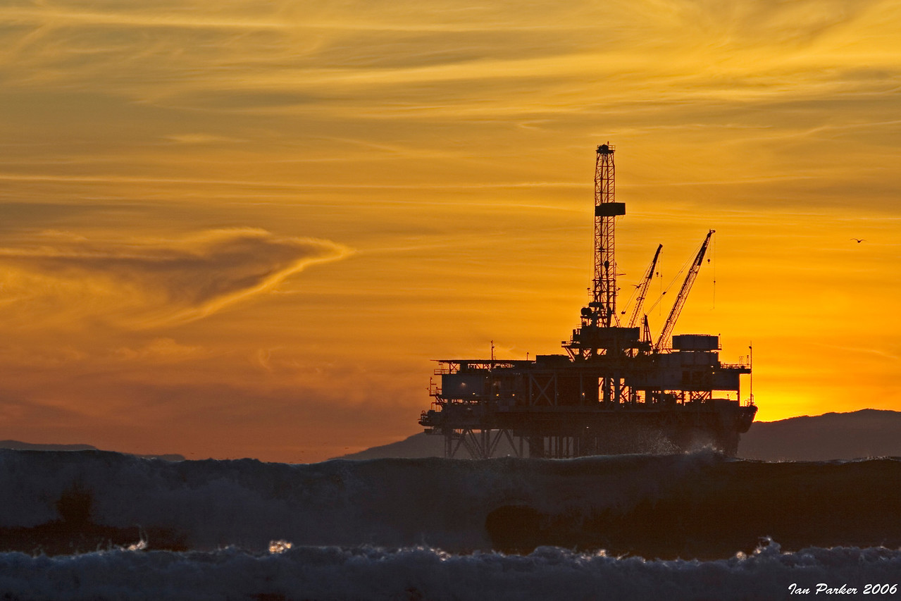 Oil rig silhouetted by  yellow sunset: Huntington Beach, California
