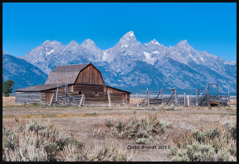barn on Mormon Run<br /> <br /> between Yellowstone NP and the Tetons  - there are probably a 100 * renditions * of how this barn looks to * artistic photographers *   this is it naturally between tourists and photographers walking in front of it - semi tractor trailors in the foot hills on the nearby highway to the Tetons - minus the old house on the left and houses on the right ...... like taking a photo of the Alamo ........ ;)