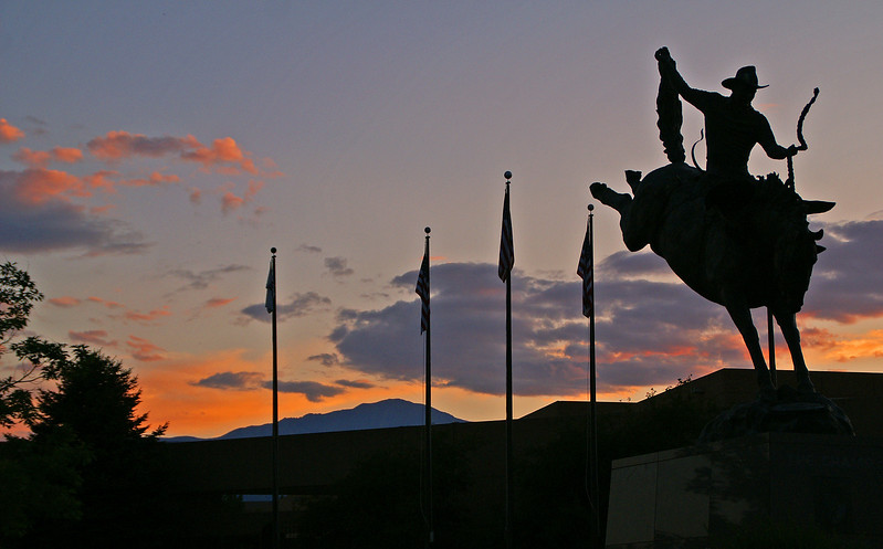 The bronze statue, at Pro Rodeo Hall of Fame, makes a nice silhouette as Pikes Peak stands guard at sunset.