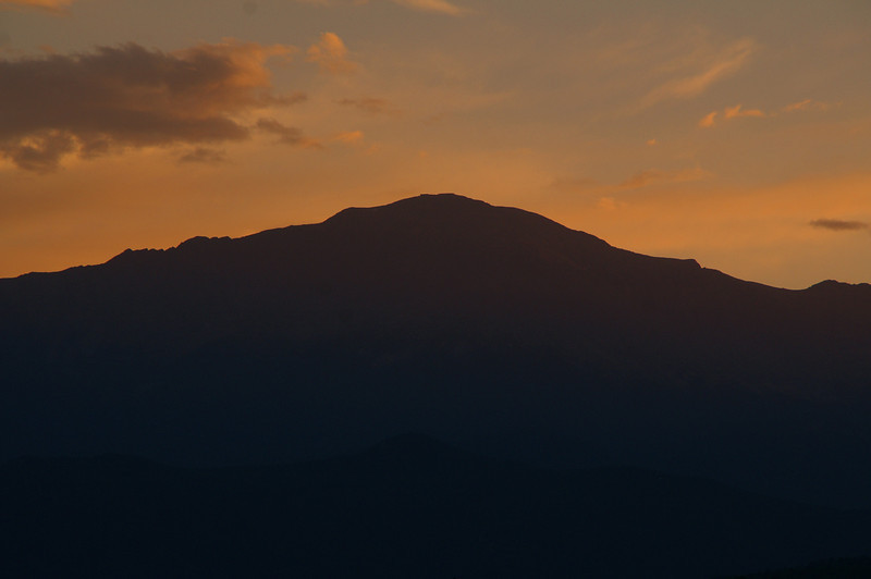 The setting sun dips below Pikes Peak in Colorado Springs.
