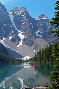 Lake Moraine View ~ A red canoe heads through the reflection of the snow packs on surrounding cliffs.