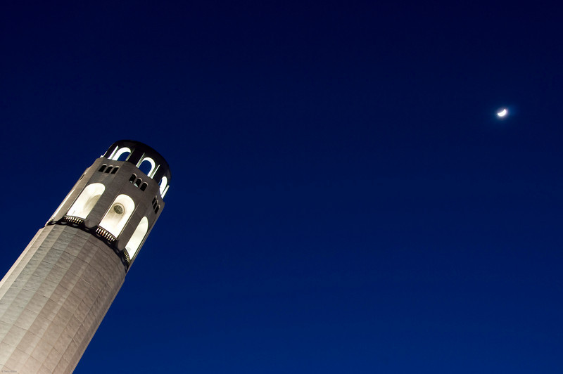 Coit Tower at night with the moon off in the distance