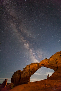 A tourist gazes at The Milky Way through Broken Arch