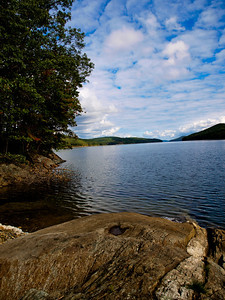 Quabbin Reservoir - Massachusetts.    Interesting story about the Quabbin Reservoir, in case you don't know.  In the 1930s, The Massachusetts District Commission decided to take over a large area of land to create a reservoir.  The water would be piped all the way across the state for use by Boston.  They paid the landowners what they (the MDC) considered to be fair.  Of course, not many landowners considered it to be fair.  Neither did renters, as they got nothing.  Over seven years, they cleared houses, trees, cemeteries, etc, and flooded the valley.  My father remembers fishing in it as the levels rose.  It is now a beautiful watershed and you can hike around and find old foundations.  There are a few books published about it, and you can find hiking trail books as well.  I was in a play about it back in the late 90s.  It is an excellent place to bike ride as well.