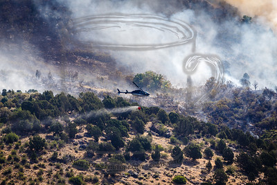 A Bell copter with a short lead to the water bucket. There's a fire fighter on the ridge at the far right, probably directing the pilot to a particular hot spot.