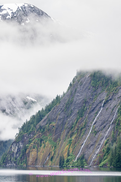 Sheer cliff faces thru the clouds of Misty Fjords.