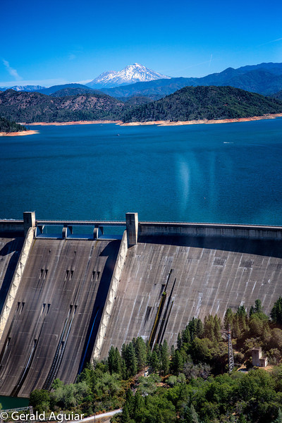 Shasta Dam in the foreground, the water of Lake Shasta, and Mt. Shasta in the background.  The blur on the right of the photo is from glare on the helicopter windshield.