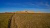 Wide areas of prairie grassland separate walls of rugged sedimentary formations; Badlands, South Dakota.