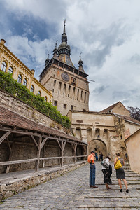 People walking uphill towards tower at Sighisoara, Romania