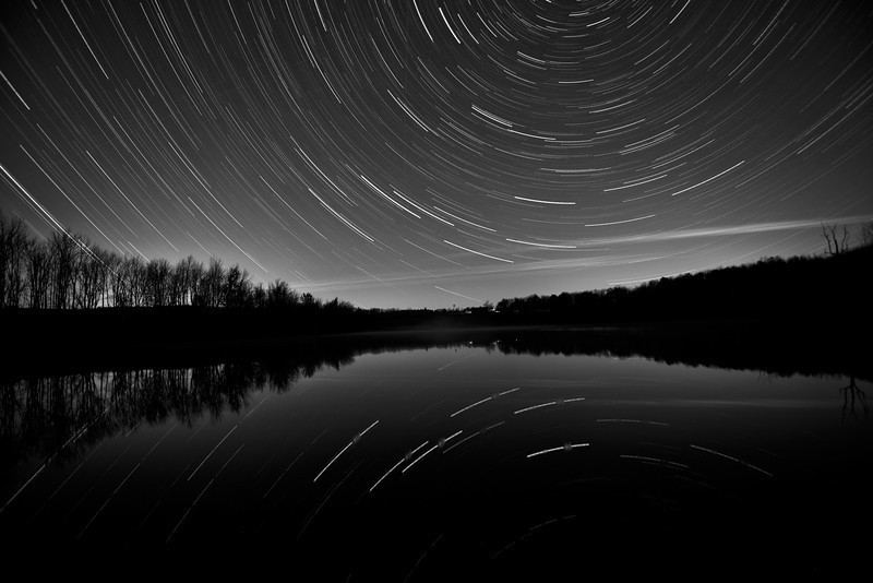 Star Trail in Columbus.  Notice a few spots where in the water the star trail is blurred. That was due to a beaver swimming by and was startled by me. He hit the water hard with his tail warning everybody around about me! The ripples caused the blurred reflection.